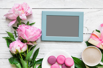 blank photo frame and peony flowers with cappuccino cup, macaroons and gift box on white wooden table. mock up