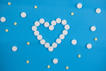Medical background with multi-colored packs of pills. Сoncept pharmacy, clinic, drugs, headache medicine. Image on illness, flu, treatment. White heart shaped pills