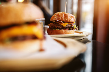Picture of delicious burgers on the table. Selective focus on burger in background.