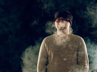 smoking man in e-cigarette smoke on black background