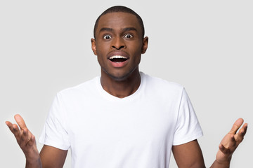 Amazed african american man with wow face feeling excited by unexpected surprise looking at camera, funny shocked black guy with open mouth stunned on isolated on white grey blank studio background