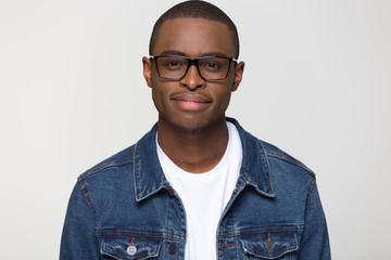 Confident young african american man wearing denim jacket and glasses looking at camera smiling, black handsome millennial smart male guy nerd isolated on blank grey white studio background, portrait Wall mural