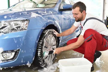customer service in the car trade: worker cleaning a vehicle // Kundendienst in der Autowerkstatt: fröhlicher Arbeiter renigt ein Fahrzeug und die Felgen