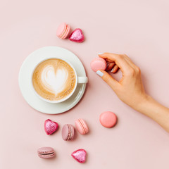 Woman's hands  holding cup of coffee on pale pink background.   Flat lay, top view