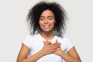 Grateful hopeful happy black woman holding hands on chest feeling pleased thankful, sincere african lady expressing heartfelt love appreciation gratitude honesty isolated on white studio background