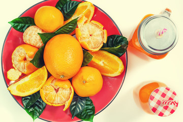Red plate with oranges and tangerines green leaves bottle with juice on light background Top view copy space