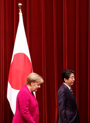German Chancellor Angela Merkel and Japan's Prime Minister Shinzo Abe leave a joint news conference in Tokyo
