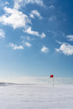 Snow covered deserted golf green with red flag, on Cleeve Hill, Cotswolds, Gloucester UK