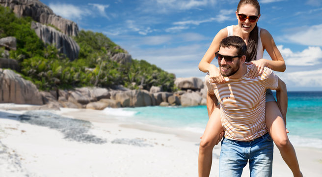 travel, tourism and people concept - happy couple having fun over tropical beach on seychelles island background