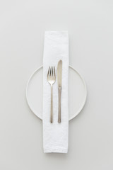 Minimal grey and white table setting with a brass cutlery set, a plate and a white napkin.