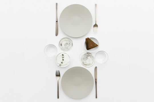 A dinner table for two with bread and cream cheese for starter, white wine and water to drink.