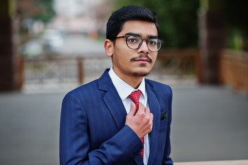 Indian young man at glasses, wear on suit with red tie posed outdoor.