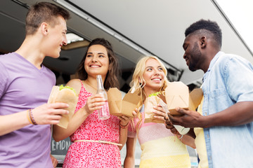 leisure and people concept - happy friends with drinks eating and talking at food truck