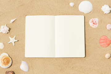 vacation, travel and summer concept - notebook with seashells on beach sand