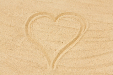 valentine's day, love and summer holidays concept - picture of heart in sand on beach