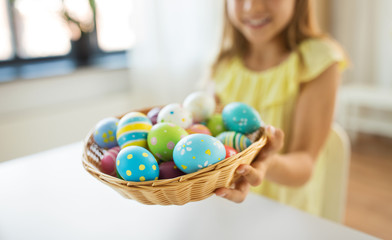 easter, holidays and people concept - close up of girl with colored eggs in wicker basket