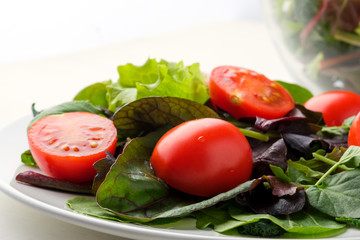 fresh colored cherry tomato salad with arugula, Basil, spinach, salad and olive oil dressing. selective focus.