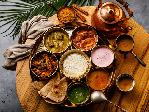 Indian food Thali  Indian-style meal with chicken meat and Masala tea Chai on wooden table