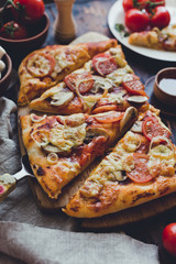 Homemade pizza with tomatoes and mushrooms, rustic style, wooden background