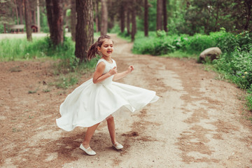Outdoor portrait of cute brunette emotional girl dancing and having fun in elegant fashionable dress. Childhood, nature, fashion concept