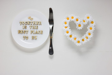 Round Plate, Cutlery and Wreath of Daisies in Heart-Shaped are on White Wooden Table Background. Text - TOGETHER THIS IS THE BEST PLACE TO BE - in Center of Plate. Concept: Love.