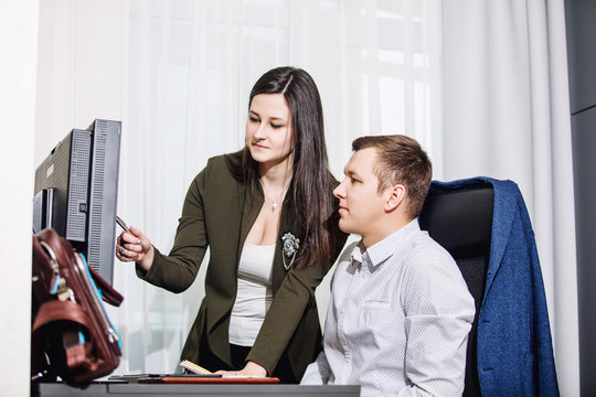 Young adult male and female businessmen at their Desk with a computer in the office during working hours