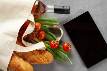 Tablet with fresh groceries in reusable bag