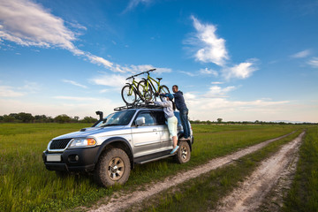 Couple taking off their bicycles from roof rack