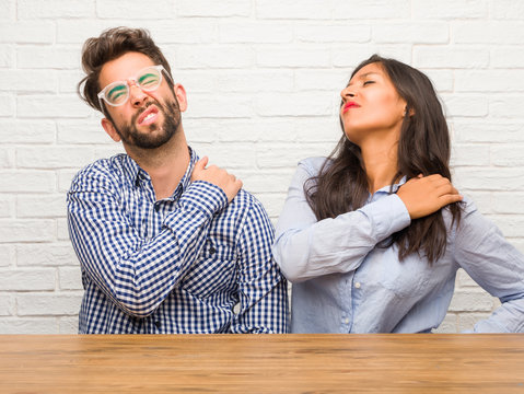 Young indian woman and caucasian man couple with back pain due to work stress, tired and astute