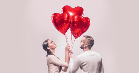 Valentine's Day. Happy joyful couple. Portrait of smiling beauty girl and her handsome boyfriend holding bunch of heart shaped air balloons