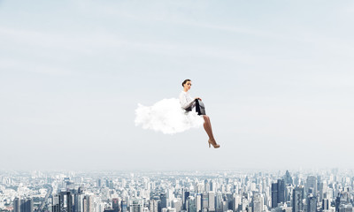 Businesswoman or accountant on cloud floating high above modern city