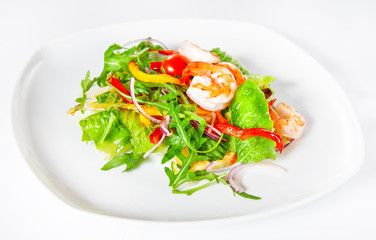 Delicious salad with shrimp, tomatoes and greenery on white