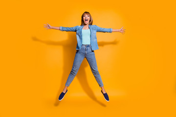 Wall Mural - Full length body size photo jumping high attractive beautiful she her lady hands arms separate in star shape figure win wearing casual jeans denim shirt clothes isolated on yellow background