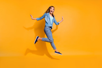 Full length body size photo yelling  jumping high beautiful she her lady little low prices announce black friday shopping store wearing casual jeans denim shirt clothes isolated on yellow background
