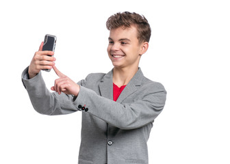 Portrait of Handsome Teen Boy talk to Mobile Phone, isolated on white background. Smiling Child standing and using Cell Phone. Cute modern Teenager taking Selfie photo on Smartphone.
