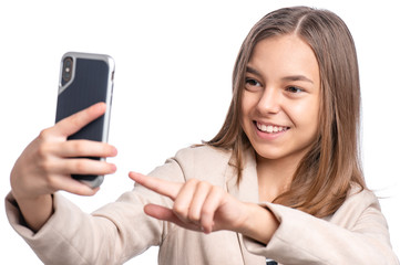 Portrait of beautiful Teen Girl talk to Mobile Phone, isolated on white background. Smiling Child standing and using Cell Phone. Pretty modern Teenager taking Selfie photo on Smartphone.