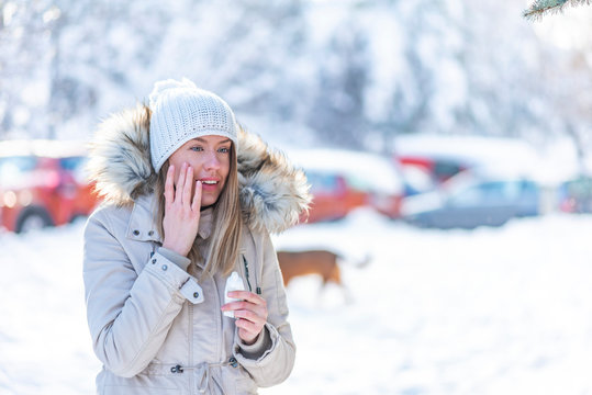 Portrait of a beautiful woman in snow with application of the protective cream in winter. Portrait of a beauty happy lady applying facial moisturizer cream in winter
