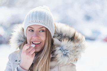 Happy woman applying lip balm in winter holiday in a snowy mountain