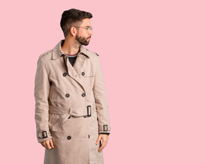 Young man wearing trench coat on the side looking to front