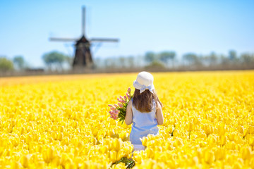 Kids in tulip flower field. Windmill in Holland