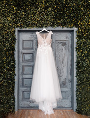 White wedding dress of bride hangs on background of door, boho and rustic style