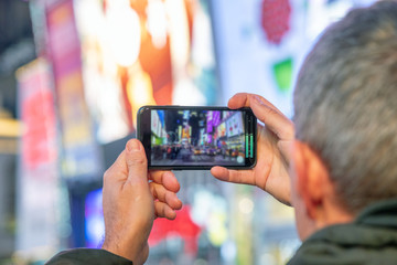 Man taking pictures of Times Square at night with smartphone