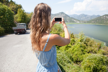 Tourist girl taking pictures on mobile phone beautiful view in Montenegro