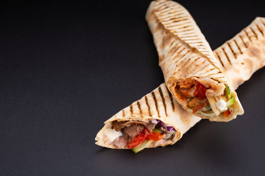 Shawarma sandwich - fresh roll of thin lavash or pita bread filled with grilled meat, mushrooms, cheese, cabbage, carrots, sauce, green. Traditional Eastern snack. On black background.