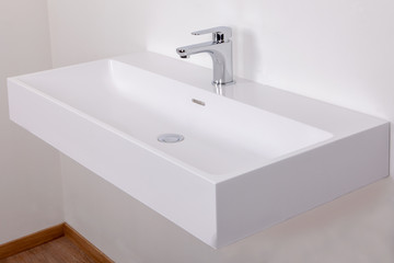 white basin with tap against on a white wall