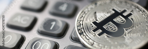 Coin crypto currency bitcoin lies on calculator keyboard background