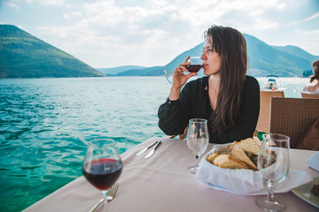 young pretty woman drinking red wine in restaurant at seaside with mountains on background Fototapete