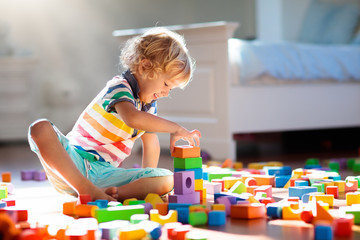 Wall Mural - Child playing with colorful toy blocks. Kids play.