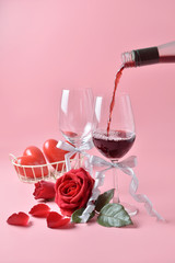 Pouring out of red wine from bottle to glass, with rose at the bottom on pink background. Concept of Valentine's Day, pop art contemporary, celebrate.