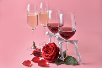 Red wine and champagne in glass, with rose at the bottom on pink background. Concept of Valentine's Day, pop art contemporary, celebrate.